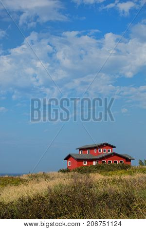 Red house in a middle of a field in Magdalen island in Canada.  Image taken from the street.