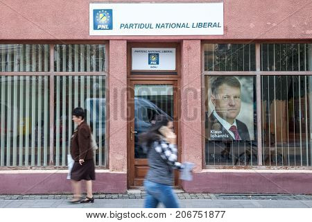 SIBIU ROMANIA SEPTEMBER 22 2017: People walking in from of the local office of PNL Party (Partidul National Liberal National Liberal Party) with a picture of Prime Minister Klaus Iohannis in front