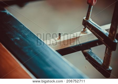 Craftsman Using Clamps Fixate Two Pieces Of Wood And Iron. The Process Of Making Desk, Furniture