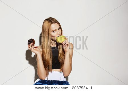 Close up portrait of handsome blonde girl in sport wear holding donuts in hands, looking in camera with flirty and sexy expression
