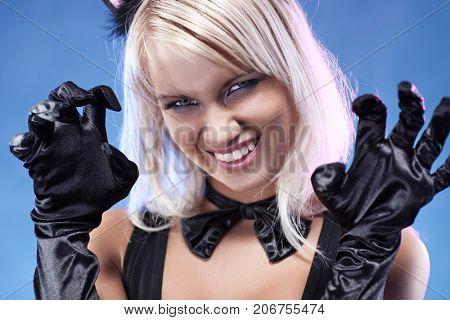 Young woman fashion portrait. Scratching kitten style.
