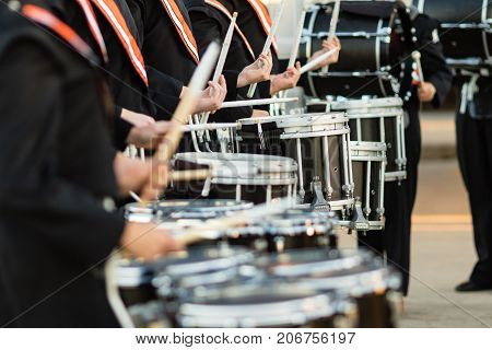 the drum sticks flashing as the drumline warms up