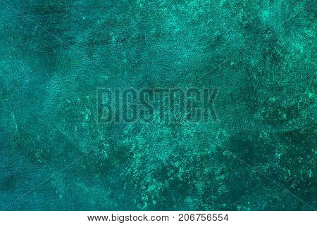 Old distressed blue turquoise rusted brass background with rough texture. Stained gradient cement or stone surface.