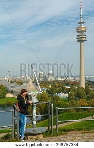 Lady tourist with backpack admiring the sights of Olympiapark on September 30 2017 in Munich Bavaria Germany.