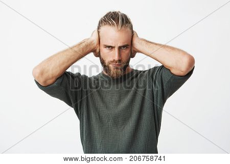 Portrait of beautiful nordic bearded guy closing ears with hands showing friend he don't want to hear his excuses for bad behaviour