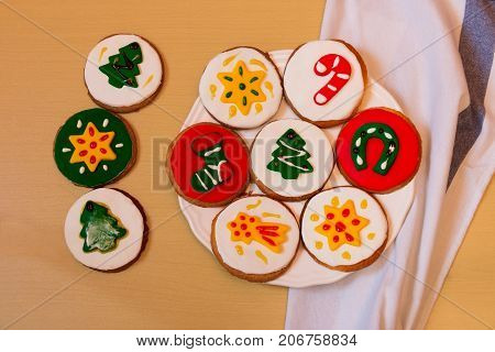Colorful christmas cookies and kitchen towel on table