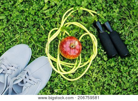 Sneakers apple and skipping rope on fresh green grass. Sports in the open air.