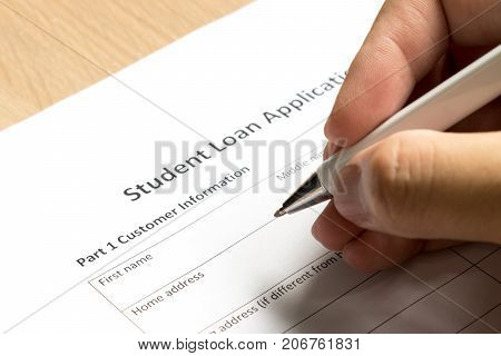 Man wait to fill information in student loan application form on desk background