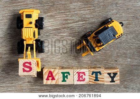 Toy plastic bulldozer hold toy block letter s to fulfill word safety with foklift on wood background