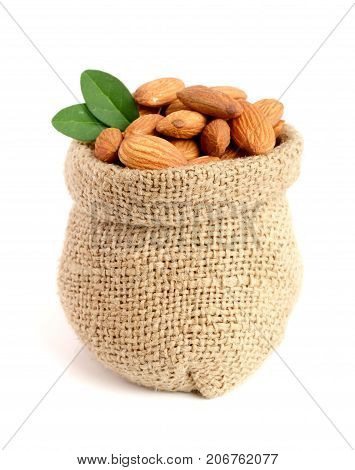 Almonds with leaf in bag from sacking isolated on white background.