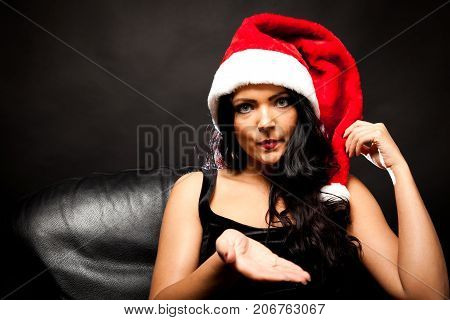 young woman with santa claus hat waiting for you to give her a gift
