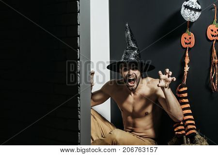Halloween man in witch hat shouting with grabbing hands. Macho with muscular torso pumpkins stockings ghost on black wall. Spirit and supernatural concept. Evil spell and magic. Holidays copy space poster