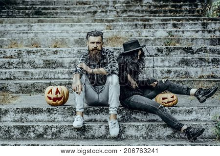 Halloween man and woman with pumpkins. Bearded hipster smoking cigarette. Couple sitting on grey stairs. Halloween holiday celebration. Bad habits and unhealthy lifestyle concept.
