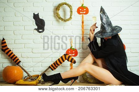 Halloween girl with pumpkins striped stockings black cat on wall. Woman in witch hat and coat sitting on floor. Evil spell and magic. Tradition and traditional symbols. Holiday celebration concept.