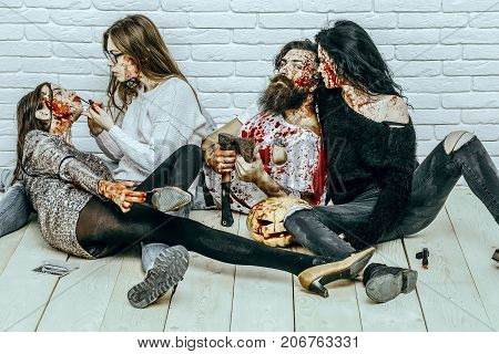 Halloween friends relaxing on wooden floor. Halloween holiday celebration concept. Bearded man with bloody pumpkin and axe. Women with red blood splatters. Girl vampire putting lip gloss makeup.