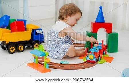 child of 1.5 years plays in the room on the floor