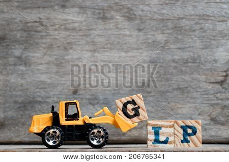 Yellow plastic bulldozer hold letter G to complete word GLP (Abbreviation Good Laboratory Practicee) on wood background