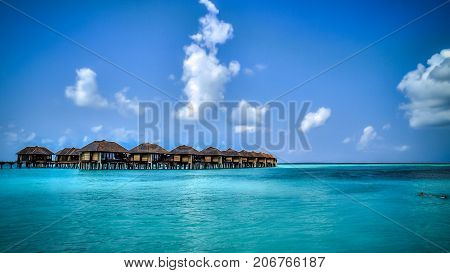View of water bungalows in tropical paradise during a hot spring day