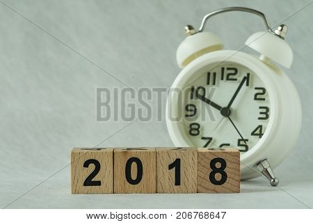 selective focus on wooden cube block 2018 with white alarm clock in the background as new year or time count down concept.