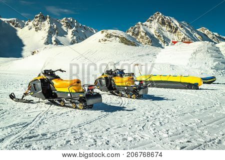 Fantastic winter landscape with yellow snowmobiles in the famous Fagaras mountains near frozen Balea lake Carpathians Transylvania Romania Europe