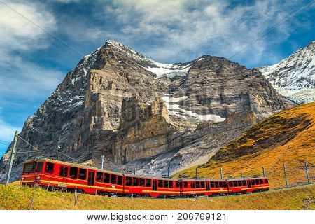 Famous express electric red tourist train coming down from the Jungfraujoch station(top of Europe) in Kleine Scheidegg tourist station Bernese Oberland Switzerland Europe