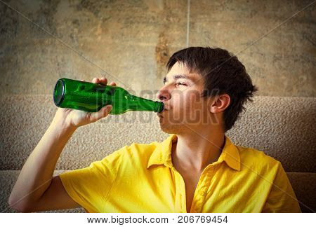 Vignetting Photo of Young Man drink a Beer on the Sofa at the Home