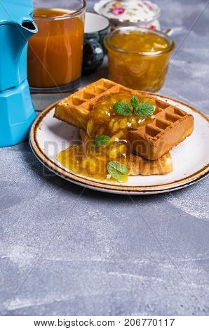 Traditional Belgian waffles with orange confiture. Selective focus.