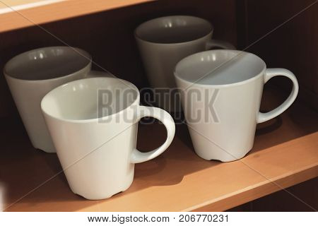 Cuisine and Food Three White Ceramic Coffee Cups on The Wooden Shelves Used for Preparing and Drinking Coffee.