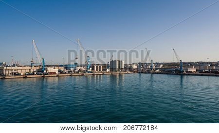 Livorno Italy - August 27 2017: Shipping industrial trade port. Crane bridge and import export container at shipping port harbor.