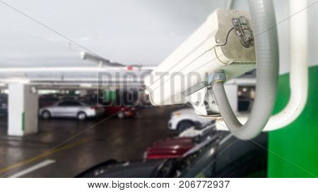 Security equipment concept. Closeup CCTV camera monitoring in the cars park. CCTV camera surveillance on car parking Safety system area control with copy space.