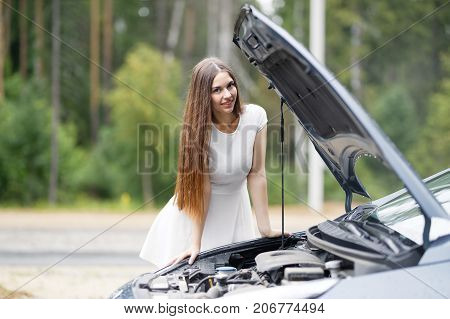 Young woman looks under the hood of his car, which broke down