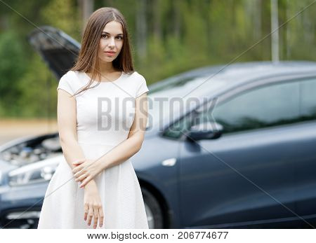 attractive woman in front of her broken car