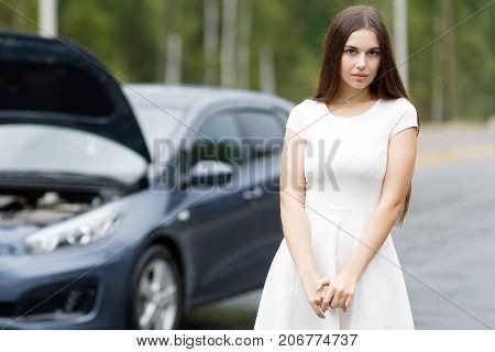 Young woman near broken car with opened hood