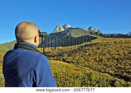 hiker with binoculars stands on a background of mountains. Svaneti Georgia