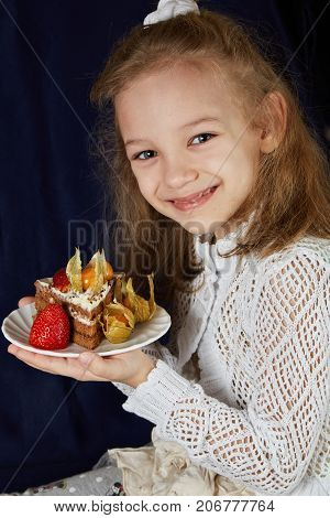 Girl in a white dress with a piece of cake on a white plate
