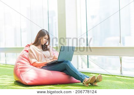 Happy beautiful Asian woman sitting on bean bag in modern office while working with laptop.