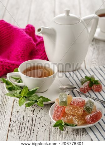 Tea Drinking. White Kettle With A Cup Of Tea With Marmalade And Mint On A White Wooden Table.