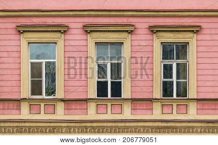 Three windows in a row on facade of urban apartment building front view St. Petersburg Russia