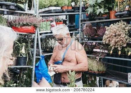 LONDON, UK - SEPTEMBER 24, 2017: Topless male flower seller at the Columbia Road Flower Market, a street market in East London that is open every Sunday.