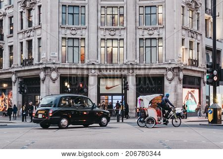 LONDON, UK - SEPTEMBER 24, 2017: Black cab and rickshaw passing in front of Nike Town, Nike's flagship store and the largest sports clothing and footwear department in Europe.