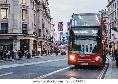 LONDON, UK - SEPTEMBER 24, 2017: Red double-decker bus on Regent Street, London. The street is decorated with NFL flags to celebrate the event and four NFL games played in capital in 2017.
