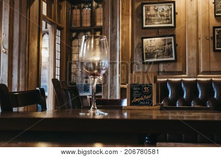CAMBRIDGE, UK - SEPTEMBER 25, 2017: Interior of The Eagle Cambridge pub, empty wine glass on the table. Opened in 1667 as the