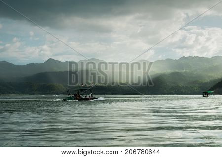 Beautiful Scenery View With Boat Move Forward In The Lake Have Sky, Sun Ray And Mountain Are Backgro