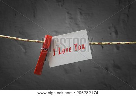I love You card attached to a rope with clothes pins on dark background.