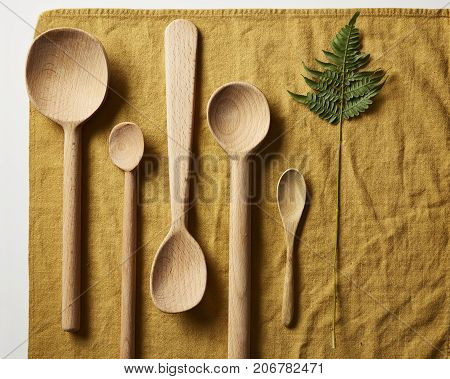 Five hand carved wooden spoons and a green leaf on a gold cloth napkin