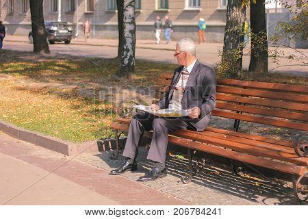 Zhytomyr Ukraine - September 05 2015: senior man reading on a bench like famous film actor forest jump