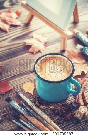 Coffee cup artist paintbrushes paints artistic canvas on easel and autumn leaves on desk.