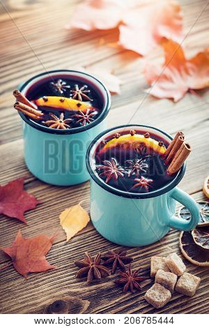 Mulled Wine In Blue Enameled Rustic Mugs With Spices And Citrus Fruit On Wooden Table With Autumn Le