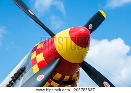 Plane nose showing propellers very colorful with a blue sky