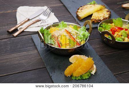 Vegan healthy food. Indian restaurant, vegetable salads in copper bowl served on wooden table